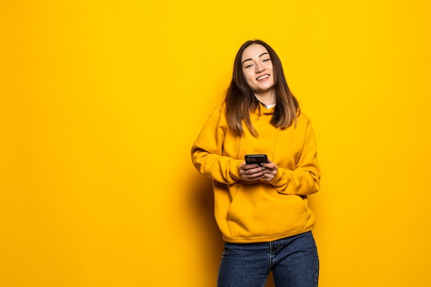 Portrait beautiful young asian woman smiles happy and uses smartphone on yellow isolated wall