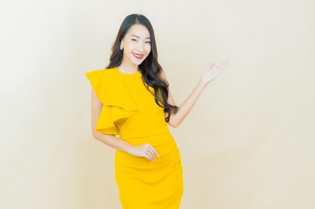 베이지색 벽에 웃는 아름다운 젊은 아시아 여성의 초상화