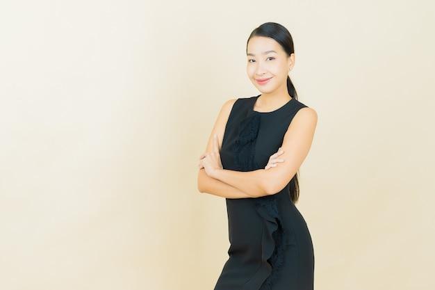 Улыбка женщины портрета красивая молодая азиатская на стене цвета