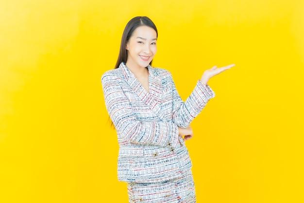 세로 아름다운 젊은 아시아 여자는 색상 벽에 미소