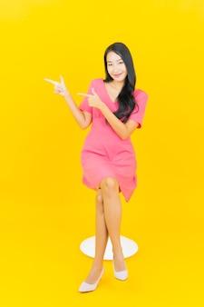 노란색 벽에 세로 아름 다운 젊은 아시아 여자 미소