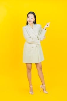 La bella giovane donna asiatica del ritratto sorride e posa sulla parete di colore