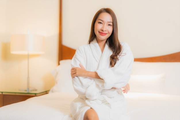 Portrait beautiful young asian woman smiles relaxing on bed in bedroom interior