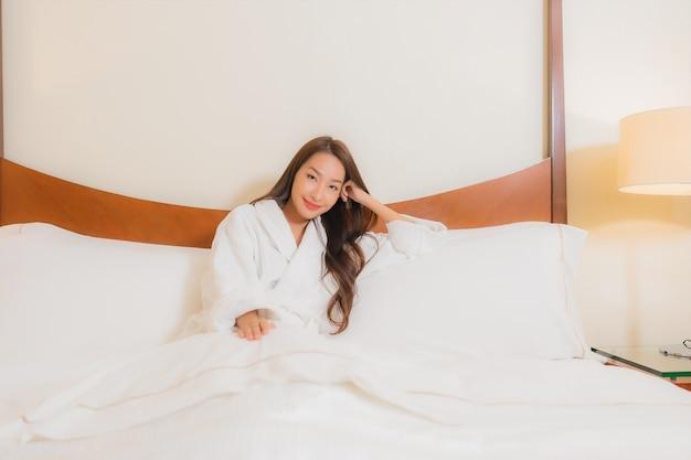 La bella giovane donna asiatica del ritratto sorride che si rilassa sul letto nell'interno della camera da letto
