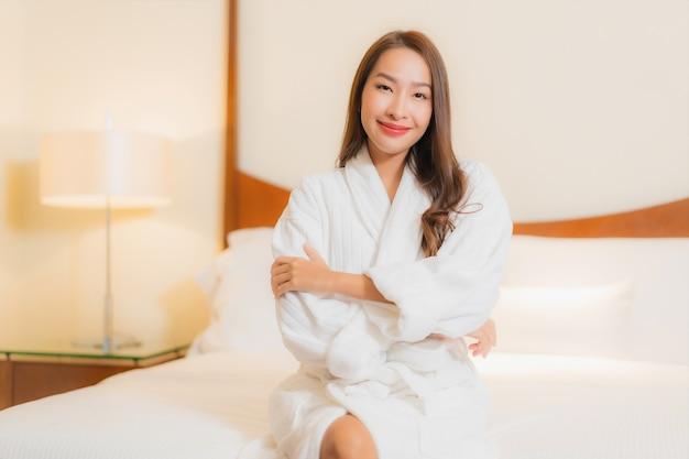 Улыбка женщины портрета красивая молодая азиатская ослабляя на кровати в интерьере спальни