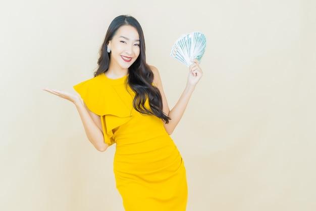Женщина портрета красивая молодая азиатская улыбается с большим количеством наличных денег и денег на бежевой стене