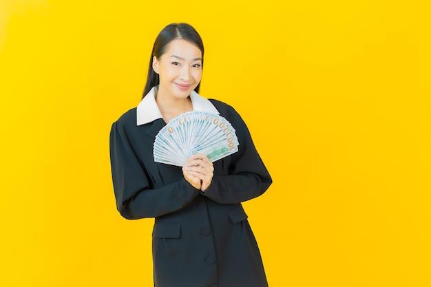 아름다운 젊은 아시아 여성이 컬러 벽에 많은 현금과 돈을 들고 미소를 짓고 있습니다.
