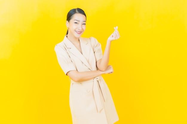 La bella giovane donna asiatica del ritratto sorride con l'azione sulla parete di colore