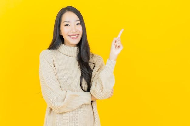 노란색 벽에 조치와 초상화 아름 다운 젊은 아시아 여자 미소