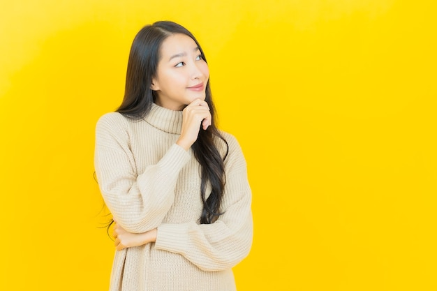 La bella giovane donna asiatica del ritratto sorride con l'azione sulla parete gialla