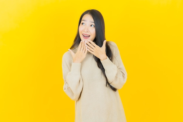 Portrait beautiful young asian woman smiles with action on yellow wall