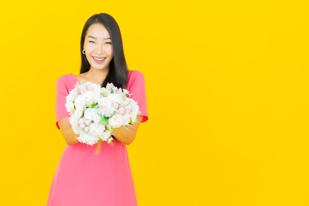 Portrait beautiful young asian woman smiles with bouquet of flowers on yellow wall