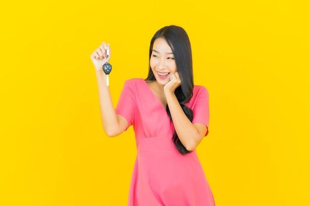 노란색 벽에 자동차 키와 세로 아름 다운 젊은 아시아 여자 미소