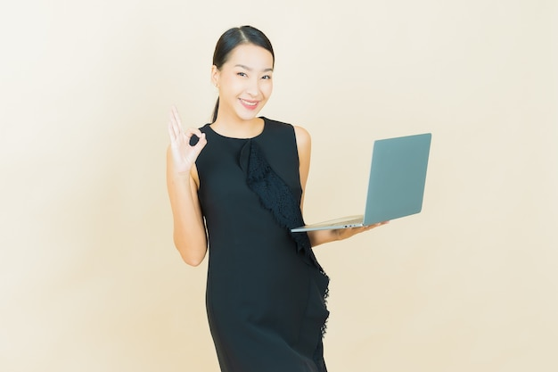 Portrait beautiful young asian woman smiles with computer laptop on isolated wall