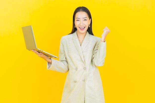 孤立した壁にコンピューター ラップトップで笑顔のポートレート美しい若いアジア女性