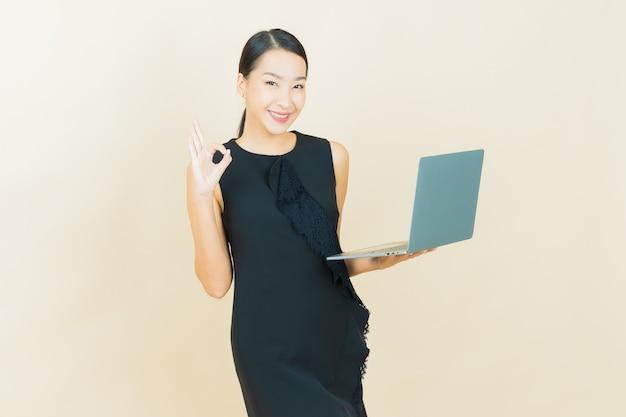 孤立した壁にコンピューターのラップトップで笑顔美しい若いアジアの女性の肖像画