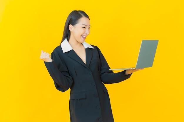 Улыбка женщины портрета красивая молодая азиатская с компьтер-книжкой компьютера на изолированной стене