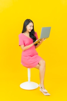 Portrait beautiful young asian woman smiles with computer laptop on yellow isolated wall