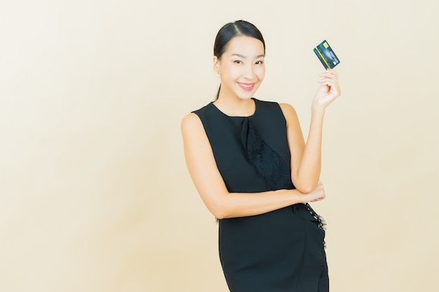 Portrait beautiful young asian woman smiles with credit card on color wall