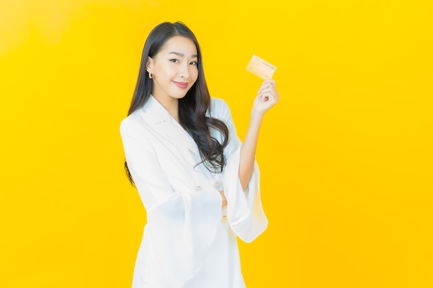Portrait of beautiful young asian woman smiles with credit card on yellow wall