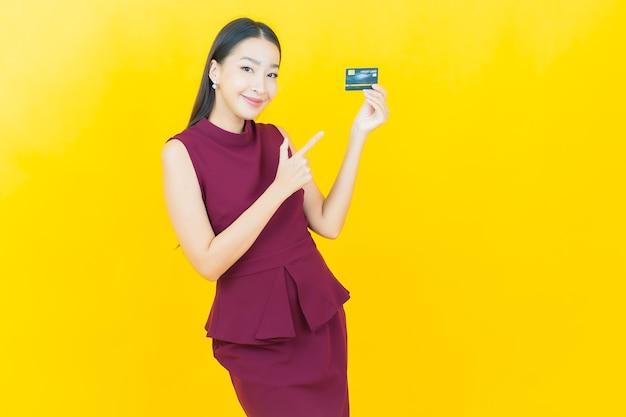 La bella giovane donna asiatica del ritratto sorride con la carta di credito sulla parete gialla