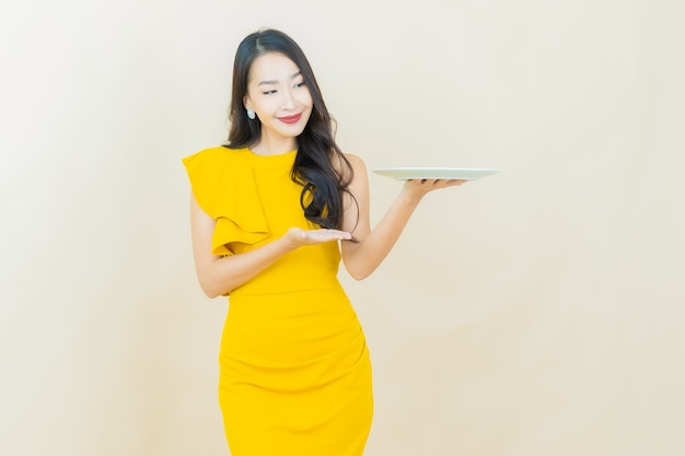 Portrait beautiful young asian woman smiles with empty plate dish on beige wall