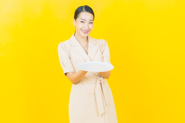 Portrait beautiful young asian woman smiles with empty plate dish on color wall