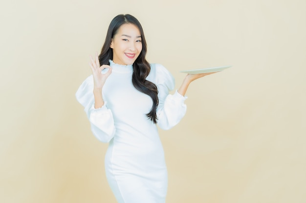 Portrait of beautiful young asian woman smiles with empty plate dish on color wall