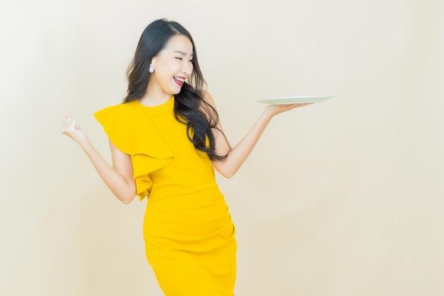 ベージュの壁に空の皿皿で笑顔美しい若いアジアの女性の肖像画