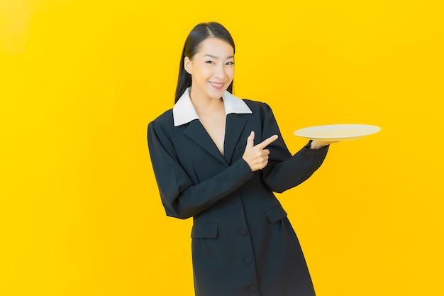 肖像画美しい若いアジアの女性は、色の壁に空の皿皿で微笑む