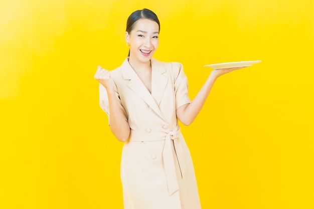 아름다운 젊은 아시아 여성이 컬러 벽에 빈 접시를 들고 미소를 짓고 있다