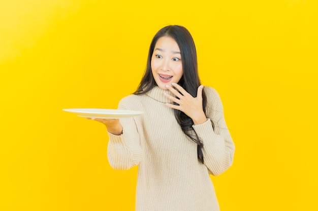 Portrait beautiful young asian woman smiles with empty plate dish on yellow wall