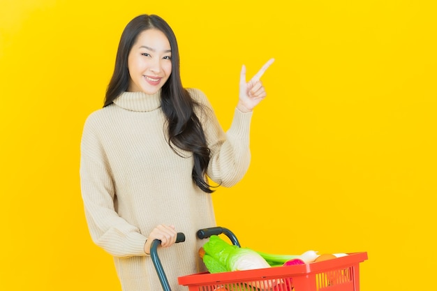 Portrait beautiful young asian woman smiles with grocery basket from supermarket on yellow wall