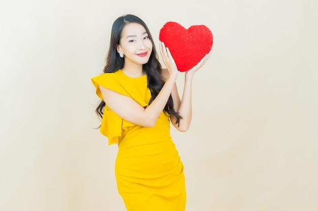 La bella giovane donna asiatica del ritratto sorride con la forma del cuscino del cuore sulla parete beige