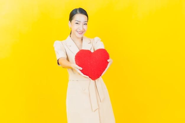 아름다운 젊은 아시아 여성이 컬러 벽에 하트 베개 모양으로 미소를 짓고 있습니다.