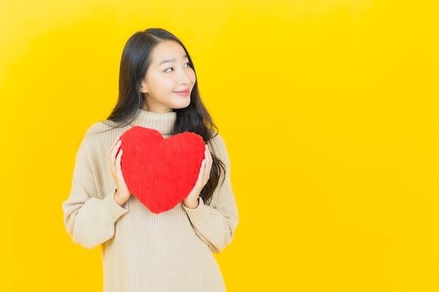 La bella giovane donna asiatica del ritratto sorride con la forma del cuscino del cuore sulla parete gialla