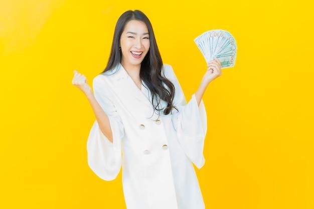 Il ritratto di bella giovane donna asiatica sorride con molti contanti e soldi sulla parete gialla