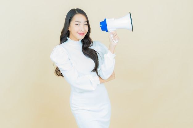 Portrait of beautiful young asian woman smiles with megaphone on color wall