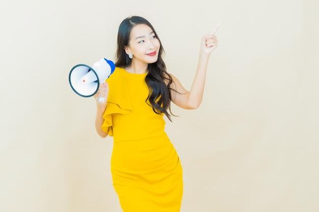 베이지색 벽에 확성기로 웃는 아름다운 젊은 아시아 여성 초상화