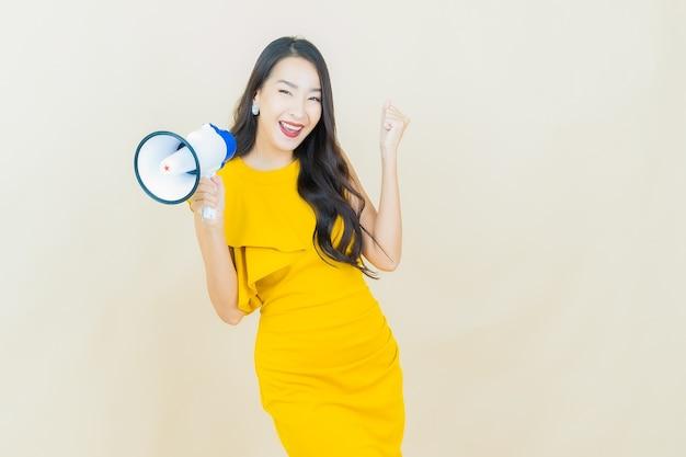 ベージュの壁にメガホンと笑顔の美しい若いアジアの女性の肖像画