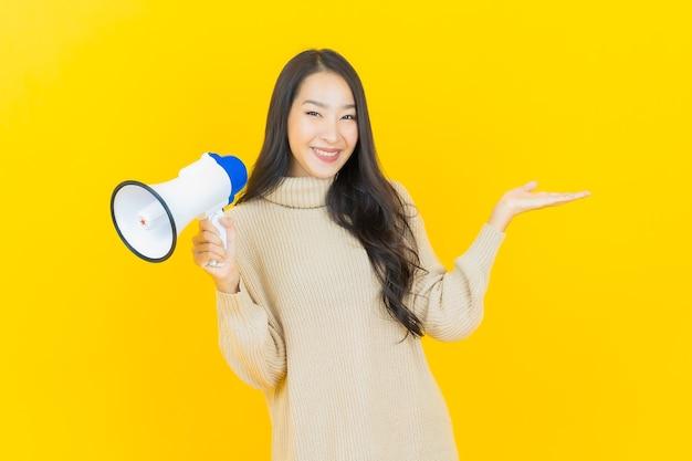 肖像画美しい若いアジアの女性が黄色の壁にメガホンで微笑む