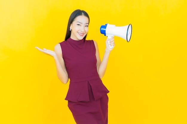 노란 벽에 확성기로 웃는 아름다운 젊은 아시아 여성 초상화