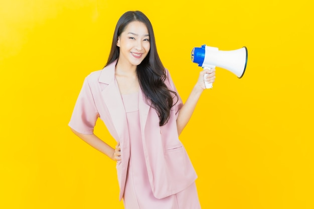 노란색 노란색 벽에 확성기로 웃는 아름다운 젊은 아시아 여성 초상화