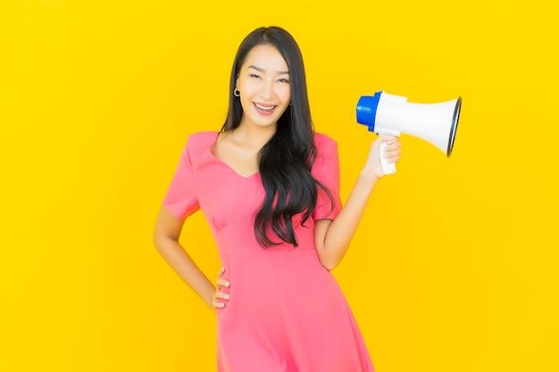 La bella giovane donna asiatica del ritratto sorride con il megafono sulla parete gialla