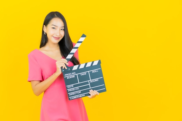 Portrait beautiful young asian woman smiles with movie slate plate cutting on yellow wall