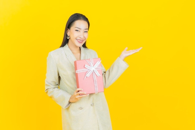 Portrait beautiful young asian woman smiles with red gift box on color wall