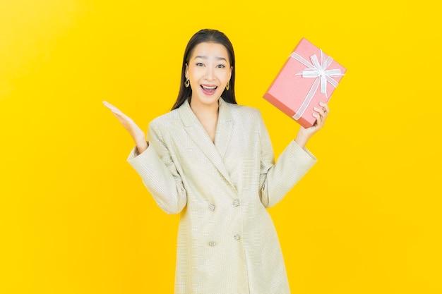 La bella giovane donna asiatica del ritratto sorride con il contenitore di regalo rosso sulla parete di colore