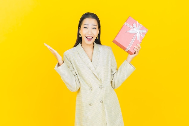 色の壁に赤いギフト ボックスで笑顔のポートレート美しい若いアジア女性