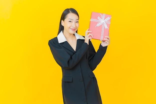 아름다운 젊은 아시아 여성이 컬러 벽에 빨간 선물 상자를 들고 미소를 짓고 있다