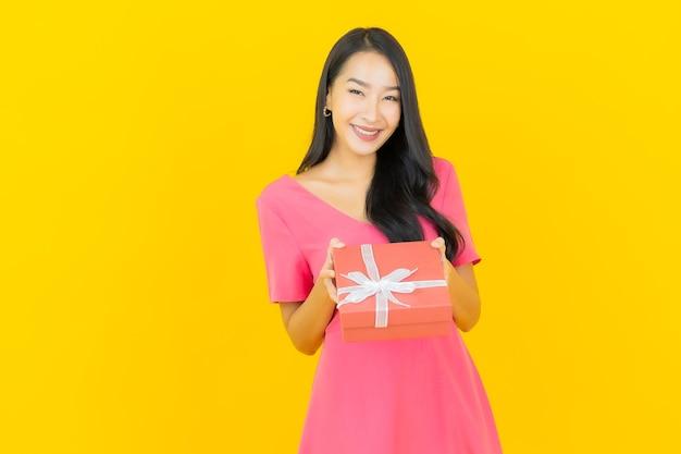 노란색 벽에 빨간색 선물 상자와 세로 아름 다운 젊은 아시아 여자 미소